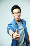Junger glücklicher asiatischer Mann, der sich Daumen zeigt Lizenzfreie Stockfotografie