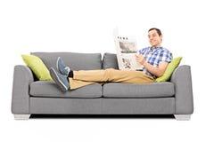 Junger glücklicher Mann, der die Nachrichten auf einem Sofa liest Stockfotos