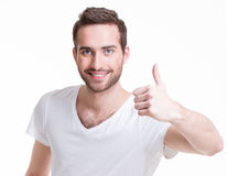Junger glücklicher Mann mit den Daumen unterzeichnen oben herein zufälliges. Stockfoto
