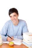 Junger glücklicher männlicher Kursteilnehmer, der von den Studienbüchern erlernt Stockfotos