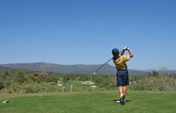 Junger Golfspieler, der einen Golfschuß schlägt Stockbild