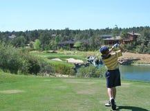 Junger Golfspieler, der einen netten Stückschuß schlägt stockfotos