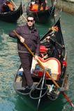 Junger Gondoliere, der japanische Touristen auf Venedig nimmt Lizenzfreie Stockfotos