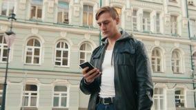 Junger grober Mann beantwortet das Telefon in einer schönen europäischen Stadt stock video