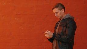 Junger grober Mann benutzt einen Smartphone vor dem hintergrund einer orange Wand stock video