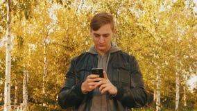 Junger grober Mann benutzt Smartphone im Park stock video