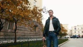 Junger grober Mann geht durch eine schöne europäische Stadt an der Dämmerung stock footage