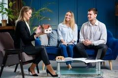Junger Grundst?cksmakler, Innenarchitekt, Dekorateur auf der Sitzung mit Kunden lizenzfreie stockfotografie