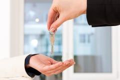 Junger Grundstücksmakler ist mit Tasten in einer Wohnung Lizenzfreie Stockfotografie