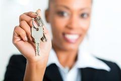 Junger Grundstücksmakler mit Schlüsseln in einer Wohnung Stockbild