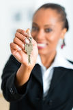Junger Grundstücksmakler mit Schlüsseln in einer Wohnung Lizenzfreie Stockbilder