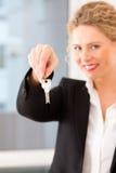 Junger Grundstücksmakler ist mit Tasten in einer Wohnung Stockfotos