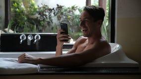 Junger gut aussehender Mann, der an der Badewanne, unter Verwendung des intelligenten Telefons, Erfolg im Abkommen, lächelnd lieg stock video