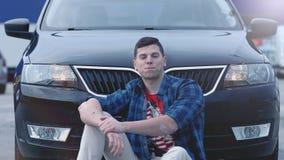 Junger gut aussehender Mann, der froh lächelt, sitzend vor seinem neuen Automobil stock footage