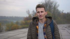 Junger gut aussehender Mann geht durch die Stadt zur bewölkten Zeit stock footage