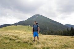 Junger gut aussehender Mann mit dem Rucksack, der im Gebirgsgrasartigen Tal auf Kopienraumhintergrund der waldigen Bergspitze des stockbild