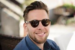 Junger gut aussehender Mann mit Sonnenbrille draußen lächelnd stockbilder