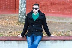 Junger gutaussehender Mann, der auf der Bank in einem schwarzen Mantel-Tragen sitzt Stockfoto