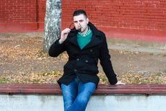 Junger gutaussehender Mann, der auf der Bank in einem schwarzen Mantel-Tragen sitzt Lizenzfreie Stockbilder