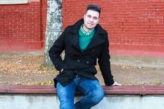 Junger gutaussehender Mann, der auf der Bank in einem schwarzen Mantel-Tragen sitzt Lizenzfreie Stockfotos