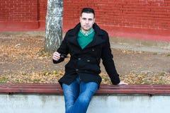 Junger gutaussehender Mann, der auf der Bank in einem schwarzen Mantel-Tragen sitzt Stockfotografie