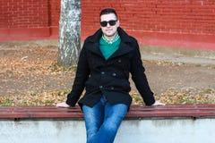 Junger gutaussehender Mann, der auf der Bank in einem schwarzen Mantel-Tragen sitzt Stockbilder