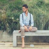 Junger gutaussehender Mann, der auf einer konkreten Bank sitzt Lizenzfreies Stockbild