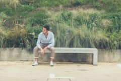 Junger gutaussehender Mann, der auf einer konkreten Bank sitzt Stockfotografie
