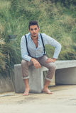 Junger gutaussehender Mann, der auf einer konkreten Bank sitzt Stockbilder