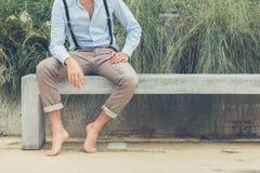 Junger gutaussehender Mann, der auf einer konkreten Bank sitzt Stockfotos
