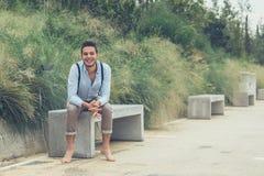Junger gutaussehender Mann, der auf einer konkreten Bank sitzt Stockbild