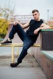Junger gutaussehender Mann, der auf einer Skateboardanlagerampe stillsteht lizenzfreie stockfotografie