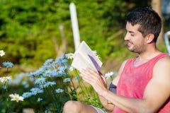 Junger gutaussehender Mann, der auf Stuhl- und Lesebuch sitzt Stockfotografie