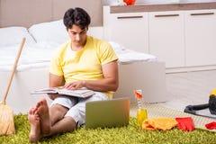 Junger gutaussehender Mann, der das Schlafzimmer säubert und am compu sitzt stockbild