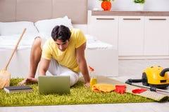 Junger gutaussehender Mann, der das Schlafzimmer säubert und am compu sitzt stockfoto