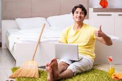 Junger gutaussehender Mann, der das Schlafzimmer säubert und am compu sitzt stockbilder