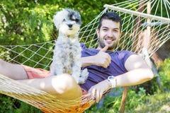Junger gutaussehender Mann, der in der Hängematte mit seinem weißen Hund sich entspannt stockbild