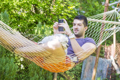 Junger gutaussehender Mann, der in der Hängematte sich entspannt und mit seinem Telefon spielt Lizenzfreies Stockfoto