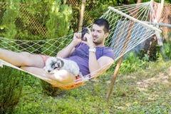 Junger gutaussehender Mann, der in der Hängematte sich entspannt und mit seinem Telefon spielt Stockfotografie