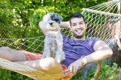 Junger gutaussehender Mann, der in der Hängematte mit seinem weißen Hund sich entspannt Lizenzfreies Stockfoto
