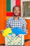 Junger gutaussehender Mann, der die zufällige Kleidung hält Wäschekorb und lächelt zur Kamera, orange Wand mit Flaggen herein trä Lizenzfreie Stockfotografie