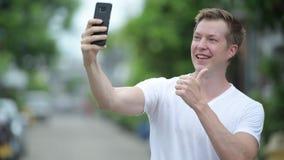 Junger gutaussehender Mann, der draußen Handy in den Straßen verwendet stock footage