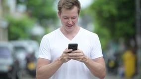 Junger gutaussehender Mann, der draußen Handy in den Straßen verwendet stock video footage