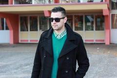Junger gutaussehender Mann, der in einem schwarzen Winter-Mantel trägt Sunglas aufwirft Stockfotos