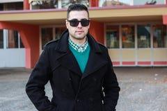 Junger gutaussehender Mann, der in einem schwarzen Winter-Mantel trägt Sunglas aufwirft Stockbilder