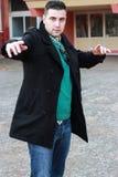 Junger gutaussehender Mann, der in einem schwarzen Winter-Mantel trägt Sunglas aufwirft Stockfotografie