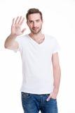 Junger gutaussehender Mann, der Halt mit seiner Hand fordert. Stockbild