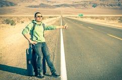 Junger gutaussehender Mann, der im Death Valley - dem Kalifornien per Anhalter fährt Lizenzfreie Stockfotos