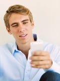 Junger gutaussehender Mann, der intelligenten Handy verwendet, Stockbilder