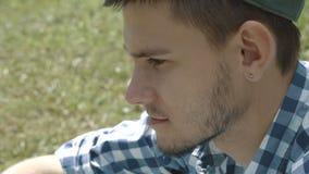 Junger gutaussehender Mann in der Kappe unter Verwendung der Tablette und des Lächelns stock video
